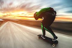 Een mens in een helm en het leer passen, in een rek bij hoge snelheid, bergaf ritten op lang longboard voor op afsalt aan tegen royalty-vrije stock afbeelding