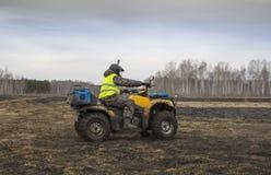 Een mens in een helm op een ATV berijdt snel in onoverschrijdbaar terrein Royalty-vrije Stock Foto's