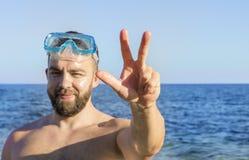 Een mens in een het duiken masker bevindt zich erachter stock foto's