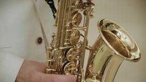 Een mens in een hoed die de saxofoon spelen stock videobeelden