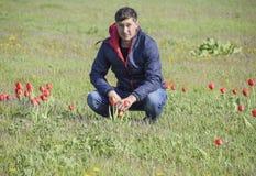 Een mens in een jasje op een gebied van tulpen Open plek met tulpen Stock Afbeelding