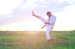 Een mens in een kimono leidt karate in aard, een mooie op zonsondergang stock afbeelding