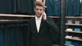 Een mens in een klassiek kostuum die op een celtelefoon spreken stock footage
