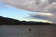 Een mens in een kleine boot uit aan overzees en vissen Royalty-vrije Stock Foto