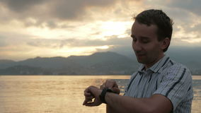 Een mens in een overhemd controleert berichten op slim horloge tijdens de zonsopgang op het strand van de oceaan en de bergen tif stock videobeelden