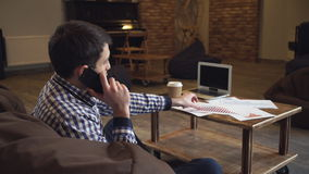 Een mens in een overhemd die een grafiek in hand houden en op de telefoon spreken stock video