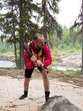 Een mens in een reddingsvest die een bijl houden en op de achtergrond van bomen gillen Royalty-vrije Stock Foto