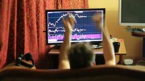 Een mens in een T-shirt en borrels, die thuis op de laag de zitten, controleren veranderingen in het programma op de muntuitwisse stock footage