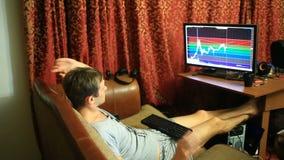Een mens in een T-shirt en borrels, die thuis op de laag de zitten, controleren veranderingen in het programma op de muntuitwisse stock video