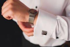 Een mens in een wit overhemd in een venster zet op cufflinks royalty-vrije stock afbeelding