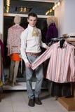 Een mens in een wit overhemd met jabot kiest kleren Stock Fotografie