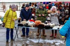 Een mens in eenvormig verkoopt de winterhoeden tijdens een nationale feestdag stock afbeelding