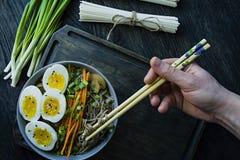 Een mens eet de noedels van boekweitsoba met saus en bijgerechten in bouillon Japans voedsel Aziatische keuken Zwarte houten acht royalty-vrije stock foto's
