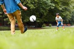 Een mens en een jongens speelvoetbal in het park stock afbeelding