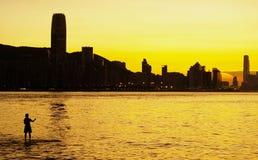Een mens en een zonsondergang van de Haven van Victoria, Hongkong Royalty-vrije Stock Afbeelding