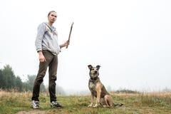 Een mens en een hondzitting en vooruit het kijken, op een weide in een mist Stock Afbeelding
