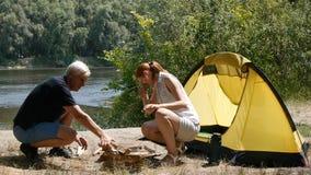 Een mens en een meisje maken een brand Toerisme, reis, groen toerismeconcept Rivier en bos op de achtergrond Wandeling, reis stock footage
