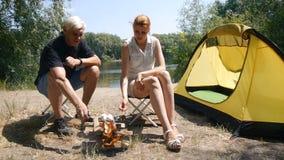 Een mens en een meisjes roosterende heemst op een brand Klaar heemst Wandeling, reis, groen toerismeconcept Gezond stock footage