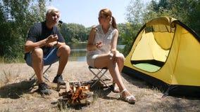Een mens en een meisjes roosterende heemst op een brand Een mens en een meisje eten heemst Wandeling, reis, groen toerisme stock footage