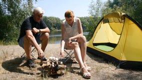 Een mens en een meisjes roosterende heemst op een brand Wandeling, reis, groen toerismeconcept Gezonde actieve levensstijl Rivier stock footage