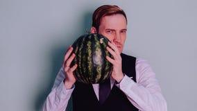 Een mens en een watermeloen/een Jongen in klassiek kostuum met een watermeloen stock fotografie
