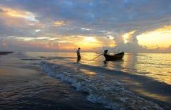 Een mens en zijn vissersboot tijdens zonsondergang Royalty-vrije Stock Afbeelding