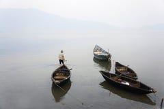 Een mens en zijn vissersboten in Vietnam Stock Afbeeldingen
