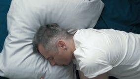 Een mens gaat naar slaap na een harde dag stock video