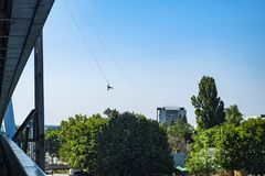 Een mens gaat onderaan het strakke koord van de brug De mens daalt op de touwladder stock foto