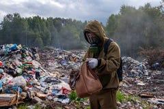 Een mens in een gasmasker onderzoekt de inhoud van de zak De arbeider is in de stortplaats Rond brandwonden en rook plastic huisv stock foto's