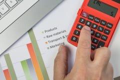Een mens gebruikt een calculator om bedrijfskosten volgens een grafiek samen te vatten Stock Foto's