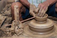 Een mens geeft aardewerk gestalte aangezien het een wiel aanzet Stock Afbeelding