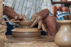 Een mens geeft aardewerk gestalte aangezien het een wiel aanzet Stock Fotografie