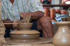 Een mens geeft aardewerk gestalte aangezien het een wiel aanzet Royalty-vrije Stock Afbeeldingen