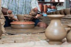 Een mens geeft aardewerk gestalte aangezien het een wiel aanzet Royalty-vrije Stock Fotografie