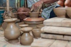 Een mens geeft aardewerk gestalte aangezien het een wiel aanzet Royalty-vrije Stock Afbeelding