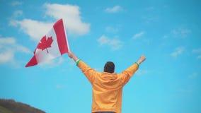 Een mens in een geel jasje, jeans en glazen bevindt zich in de bergen, houdt de vlag van Canada en toont een overwinning stock footage