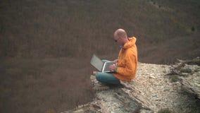 Een mens in een geel jasje, jeans en glazen zit op de rand van een klip en werkt aan laptop stock videobeelden