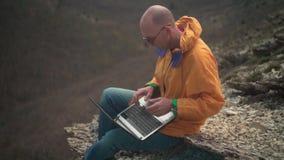 Een mens in een geel jasje, jeans en glazen zit op de rand van een klip en werkt aan laptop stock footage