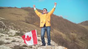 Een mens in een geel jasje, jeans en glazentribunes op een berg, wordt de vlag van Canada geplaatst in de grond stock video