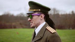 Een mens gekleed in belachelijke militaire eenvormig zegt iets aan militairen stock video