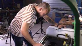 Een mens in gestreepte t-shirt die aan scherpe houten machine werken De mens is gewaagd met baard stock video