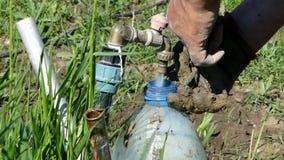 Een mens giet water in een plastic ton van een gebiedstapkraan in de zomer stock videobeelden