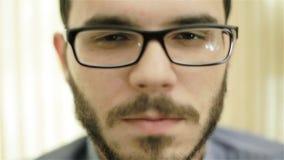 Een mens in glazen die zijn ogen en het spreken sluiten stock video