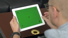 Een mens in glazen zit met een tablet, op het scherm waarvan chromakey met tellers stock videobeelden