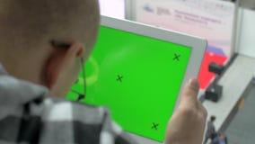 Een mens in glazen zit met een tablet, op het scherm waarvan chromakey met tellers stock video