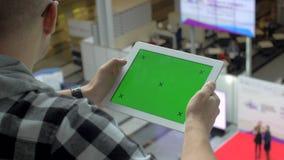 Een mens in glazen zit met een tablet, op het scherm waarvan chromakey met tellers stock footage