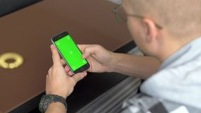 Een mens in glazen zit met een telefoon, op het scherm waarvan chromakey met tellers, stock footage