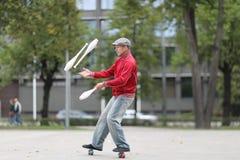 Een mens in een GLB jongleert met met clubs stock afbeeldingen