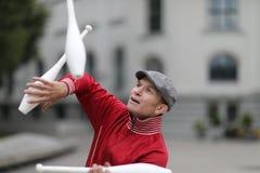 Een mens in een GLB jongleert met met clubs royalty-vrije stock foto's